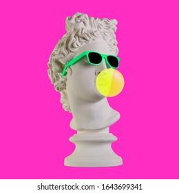 Estatua sobre un fondo rosa. Estatua de yeso de la cabeza de Apolo. Hombre. Creativo. Estatua de yeso de la cabeza de Apolo con gafas de sol. Arte conceptual mínimo.