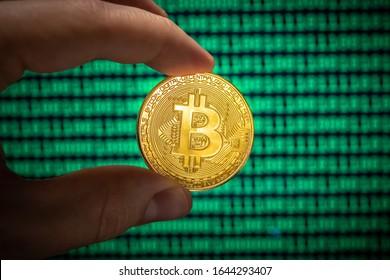 Mano sosteniendo un solo bitcoin dorado físico frente a una pantalla verde de bits unos y ceros