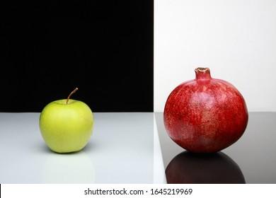 黒、グレー、白の背景にある2つのジューシーなリンゴ(ザクロと青リンゴ)についての芸術的でシンプルな写真。スタジオで作られた、カラー写真。