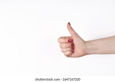 Nahaufnahme der weiblichen Hand, die Daumen oben Zeichen gegen weißen Hintergrund zeigt.