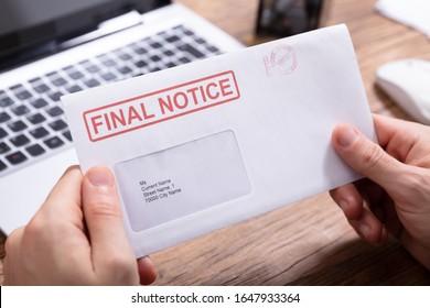 Close-up de la mano de la persona sujetando el sobre de aviso final