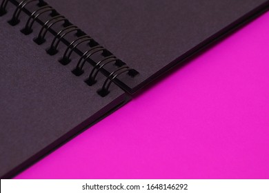 Black notebook with a spring. Artist's album on a bright purple background.