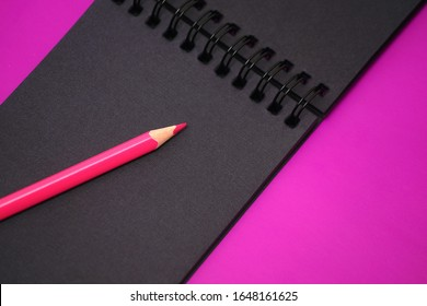 Black notebook with black sheets. Album and pencil on a purple background. Notebook sketch for the artist. Sketchbook with a spiral. Stylish bright background.