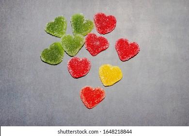 黒板背景に砂糖でマーマレードハート。マーマレードのマルチカラースイーツ。バレンタイン・デー。デザート。赤、緑、黄色のスウィートハート。