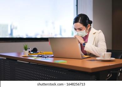 若い大人のアジアのビジネスエレガントな女性。コロナウイルスと午後2.5のマスクで病気。ラップトップコンピュータを備えた職場の机。座っている実業家は、白いスーツとピンクのウィンドウライトを着用しています。