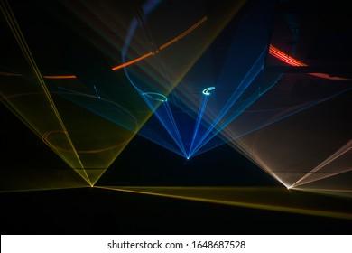 Rote, blaue, orange Laserlichter tanzen durch die Luft