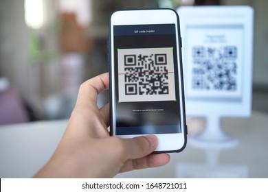 La mano de la mujer utiliza una aplicación de teléfono móvil para escanear códigos QR en las tiendas que aceptan pagos digitales sin dinero y etiquetas de plástico en la mesa. Concepto de tecnología de pago y efectivo con código QR