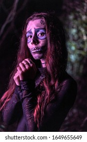 Halloween, portrait of a young woman dressed as a Mexican skull with purple lighting
