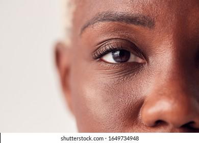 Schließen Sie oben auf den Augen der jungen Frau mit gefärbtem Haar im Studio
