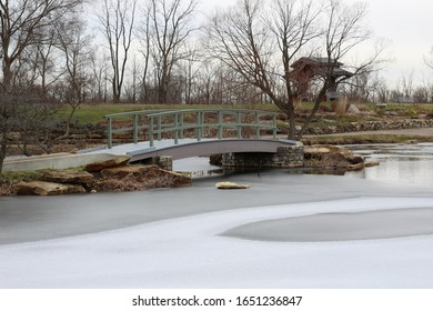 The wooden bridge over the frozen pond in the park on a cloudy gloomy winter day.