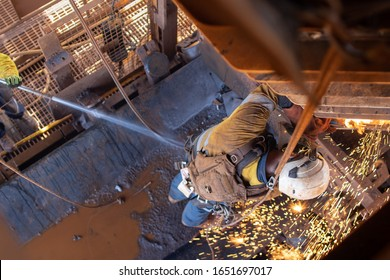 Work safety practise spotter, firewatch personal holding firehose spraying water  at the conveyor belt to controlling fire breakout during welder wearing PPE conducting oxy cutting metal repairing