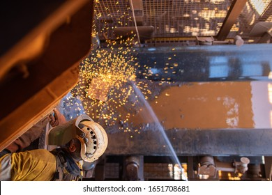 Work safety practise spotter, firewatch personal holding firehose spraying water where spark frames dropping onto the conveyor belt during welder wearing PPE conducting oxy cutting metal repairing