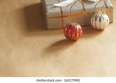 茶色の手紙の上のクリスマスプレゼントボックスとボールのクローズアップ