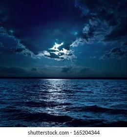 Mondlicht über dunklem Wasser in der Nacht