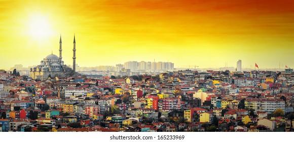 Mezquita de Estambul Suleymaniye con colorida zona residencial en puesta de sol con cielo naranja