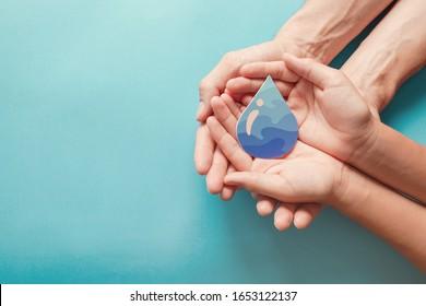 水滴を握る手、世界水の日、きれいな水と衛生、コロナウイルスのパンデミックのための手指消毒剤と衛生、家族の手を洗う、CSR、節水、きれいな再生可能エネルギーの概念