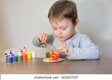 Cute, little beautiful child draws Easter eggs with colored paint. The boy is sitting at the table and enthusiastically engaged in creativity, preparing for Easter.