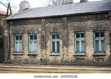 Gealterte verwitterte Straßenmauer mit einigen Fenstern