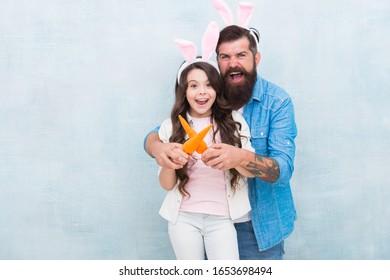 うさぎの衣装で楽しんでいます。お父さんと子供はバニーの耳を着ています。私の小さなウサギのためのニンジン。コピースペース。春の気分。イースターファミリーパーティー。幸せなイースターの概念。父と娘は健康的な食べ物を食べています。
