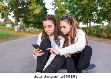 Chicas novias adolescentes, verano en el parque, video en el teléfono, descanso después de la escuela. SMS en el teléfono inteligente. Leer escribir mensaje, redes sociales en línea en Internet. Patineta, fondo de camino de árboles