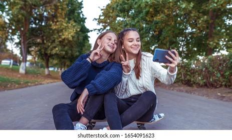 Chicas novias adolescentes, parque de verano, fotos de teléfonos inteligentes, sonriendo feliz, divirtiéndose jugando. Teléfono Selfie. Grabar mensaje de video, redes sociales en línea Internet. Patineta, fondo de camino de árboles