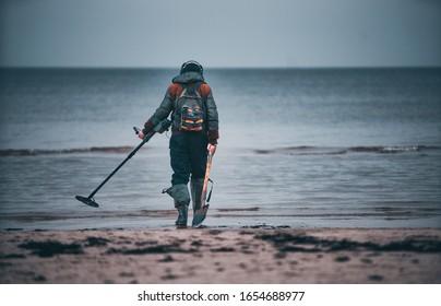 Hombre con un detector de metales en una playa de arena.