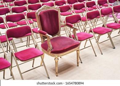 Unieke troon- of ceremoniële fauteuil met fluwelen zitting en gouden details tussen vele eenvoudige identieke vergelijkbare stoelen. Uniek concept.