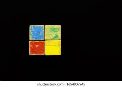Los bloques de niños viejos y rayados (rojo, azul, verde y amarillo) se colocan sobre un fondo negro. Todos juntos parecen similares al logotipo de un sistema operativo conocido.