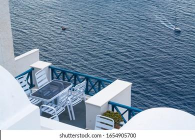 Santorini Griechenland Home Patio mit Meerblick als Kreuzfahrtschiff Tender Transports Touristen unten.