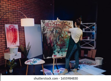 A young female artist is creating an abstract painting. She is working in the loft space with dimmed lights. She is using oil paint and a brush.
