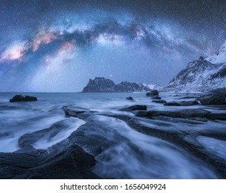 Milchstraße über den schneebedeckten Bergen und dem felsigen Strand im Winter in der Nacht in den Lofoten-Inseln, Norwegen. Landschaft mit blauem Sternenhimmel, Wasser, Steinen, schneebedeckten Felsen, heller Milchstraße. Schöner Raum