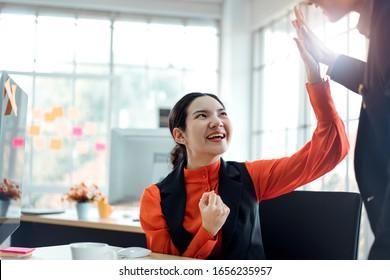 若いアジアの大人のビジネスウーマンは、プロジェクトの仕事が成功した後、男性チームのマーケティングに触れます。彼女は幸せで笑顔のペルソナです。最小限のオフィスウィンドウの明るい背景。