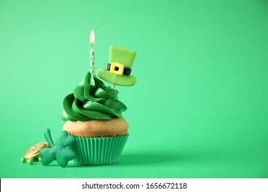 Decorated cupcake on green background, space for text. St. Patrick's Day celebration