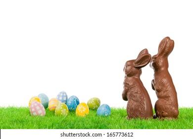 牧草地にカラフルな卵とチョコレートのイースターのウサギのカップル。