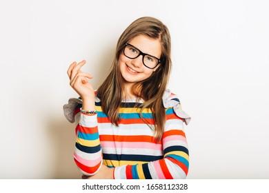 Studio portret van mooi jong meisje, het dragen van een bril en kleurrijk streep shirt met lange mouwen