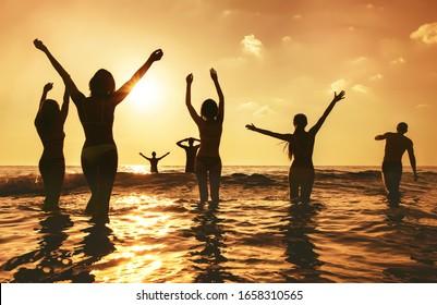 幸せな人々の大きなグループが日没の海のビーチに立っています。腕を上げたシルエット