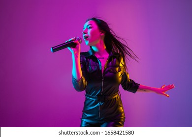 ネオンの光の中で紫色のスタジオの背景に分離された白人女性歌手の肖像画。マイク付きの黒の摩耗の美しい女性モデル。人間の感情、表情、広告、音楽、アートの概念。