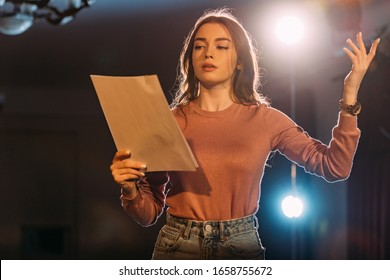 劇場の舞台で若い女優の読書シナリオ