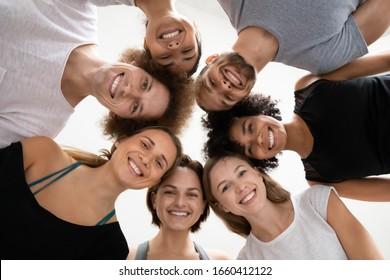 Verschiedene Leute in Aktivkleidung, die im Kreis stehen, schauen in die Kamera, Mädchen Jungs in der Yoga-Klasse zeigen Teamgeist Einheit, bereit, Training im Fitnessstudio zu beginnen, motiviert durch gutes Teamwork-Ergebniskonzept