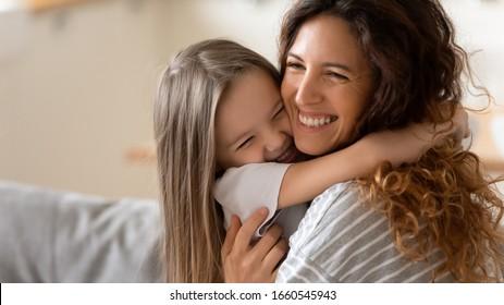 Nettes kleines Mädchen umarmen kuscheln aufgeregte junge Mutter zeigen Liebe und Zuneigung, lächelnde Mutter und lustige kleine Tochter im Vorschulalter haben Spaß zu Hause Umarmung teilen engen zarten Moment zusammen