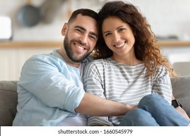 Familienporträt des glücklichen tausendjährigen Ehemanns und der glücklichen Ehefrau sitzen auf der Couch umarmen Kuschelblick auf Kamera posiert, lächelndes junges Paar umarmt zeigen Liebesliebe, entspannen zu Hause am Wochenende zusammen