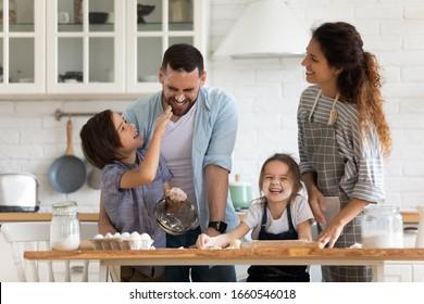 Una familia joven llena de alegría con niños pequeños en edad preescolar se divierten cocinando para hornear pasteles o tartas en casa juntos, los padres sonrientes felices disfrutan del juego de fin de semana con niños pequeños que cocinan en la cocina de panadería