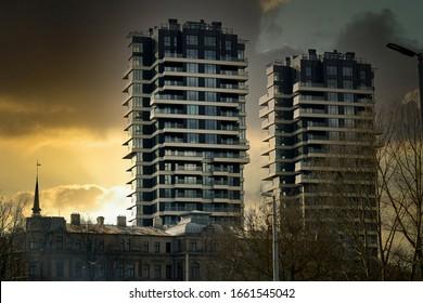 Edificio de cristal moderno con la ciudad reflejada por la noche y el cielo al atardecer.