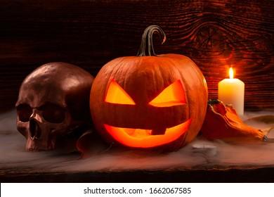 Halloween achtergrond. Enge pompoen en griezelige schedel op houten baclground.