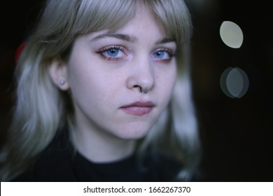 Closeup portrait of a beautiful blonde girl with long curly hair at night with neon lights of the evening city