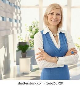 カメラに笑顔のオフィスで青い立っているエレガントな金髪の女性。