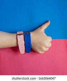 透明な青とピンクの背景に手に磁気センサーを備えた青とピンクのシリコン時計。ジェンダー平等と健康的なライフスタイル。手はスーパーサインを示しています
