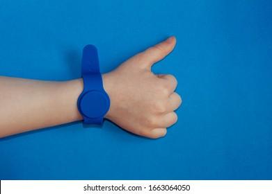 透明な青色の背景に手に磁気センサーが付いている青いシリコーン時計。モノクロ画像。健康的な生活様式。手はスーパーサインを示しています