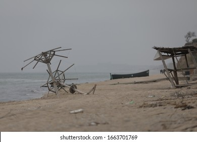 Sandstrand am Meer. Holzboot am Pier. kaputte Sonnenschirme. bewölkter Himmel und leichte Brise. Um Frische und Leere. Die Atmosphäre nach einem Hurrikan oder Sturm.
