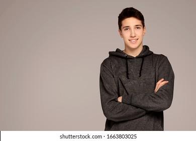 灰色の背景の上にポーズをとるパーカーのハンサムな10代の少年の肖像画。スタジオショット。十代のファッション。